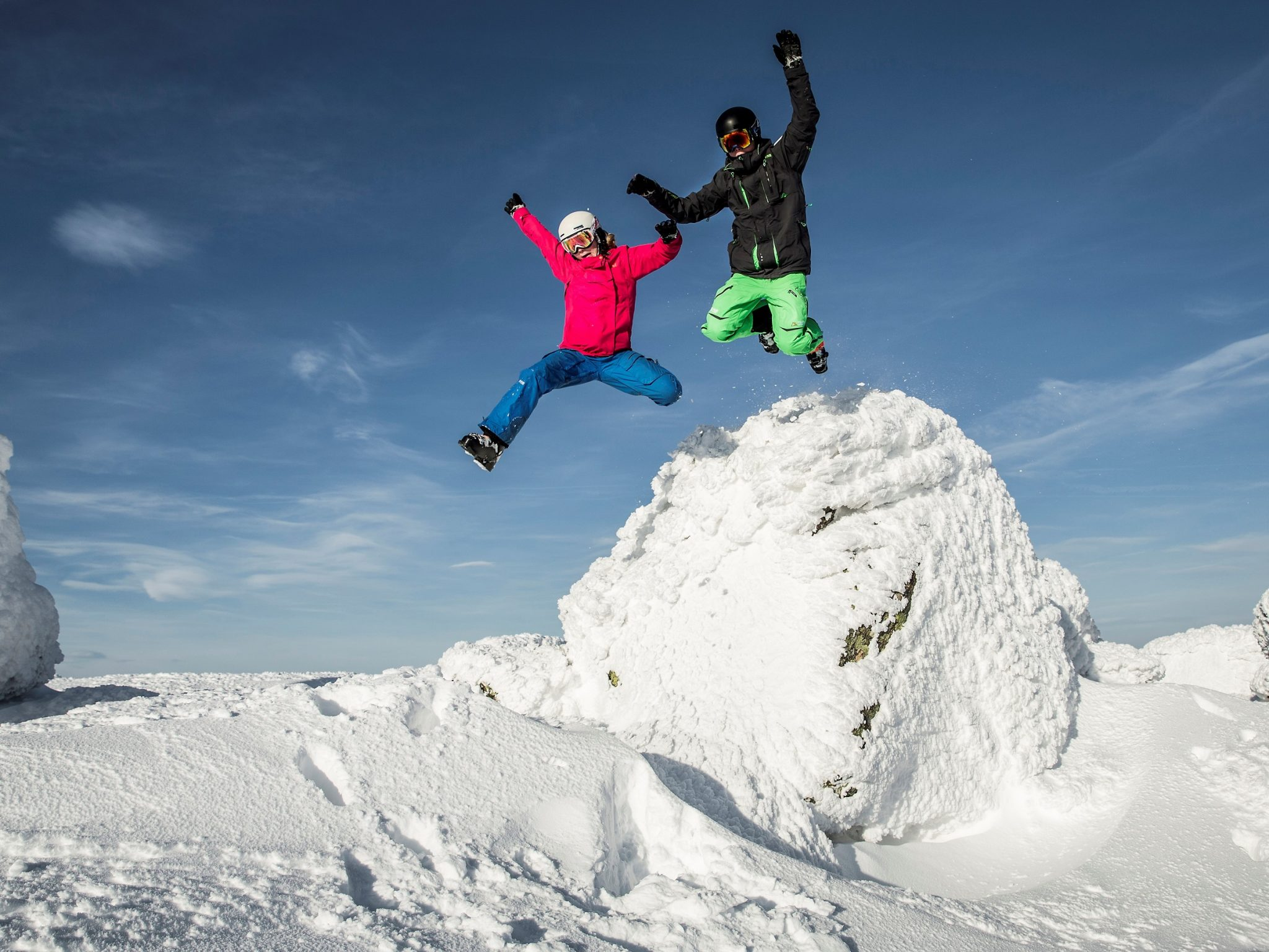 Two children jump from a snow pile