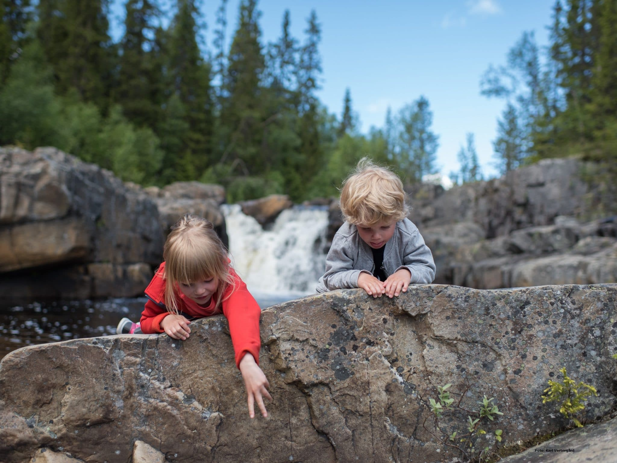Two children play at a waterfall in Vemdalen