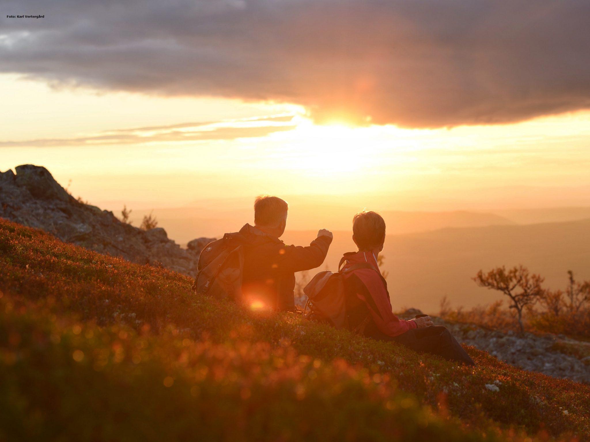 Två personer njuter av solnedgång en höstkväll i Vemdalen