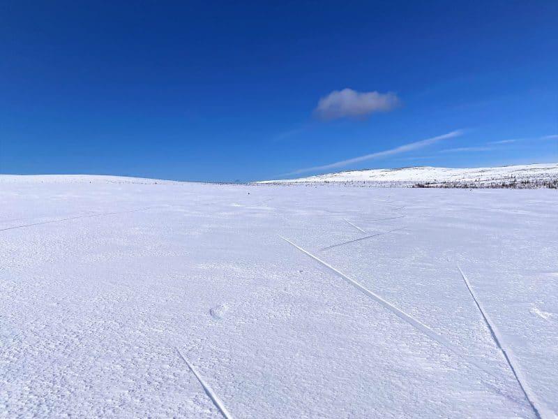 Vy över snötäckt fjäll med blå himmel en vårdag i Vemdalen