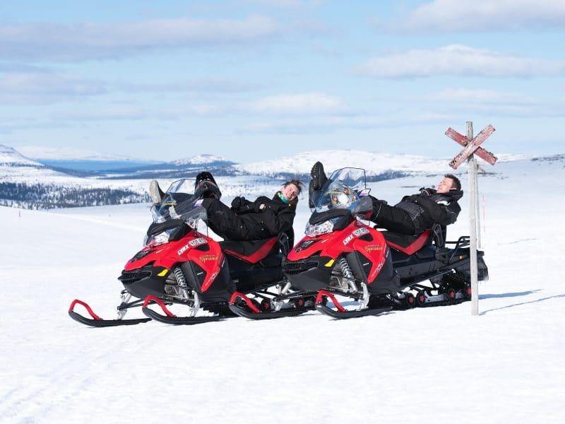 Two men are sunbathing on snow mobiles in Vemdalen