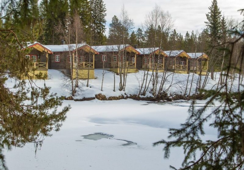 Winter view of Vålkojan's small cottages in Vemdalen